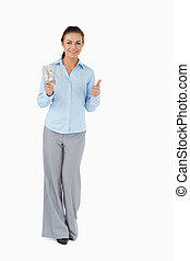 Smiling businesswoman with banknotes giving thumb up