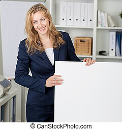 Smiling Businesswoman With Billboard In Office