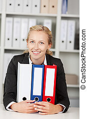 Smiling Businesswoman With Binders Sitting At Desk