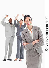 Smiling businesswoman with cheering colleagues behind her