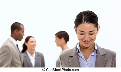 Smiling businesswoman with co-workers behind her