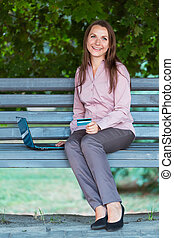 Smiling businesswoman with computer laptop and credit card on the bench in the park