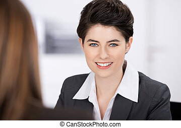Smiling Businesswoman With Coworker In Foreground