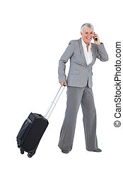 Smiling businesswoman with her luggage and calling someone