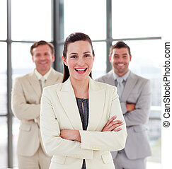 Smiling businesswoman with her team in the background