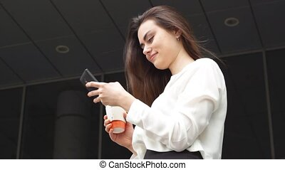 Smiling businesswoman with hot drink using smartphone -...