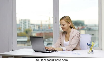 smiling businesswoman with laptop and papers