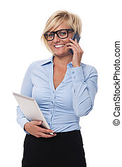 Smiling businesswoman with mobile phone and digital tablet
