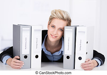 Smiling businesswoman with office binders