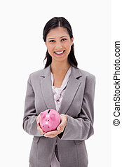 Smiling businesswoman with piggy bank