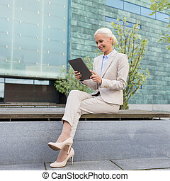 smiling businesswoman with tablet pc outdoors - business,...