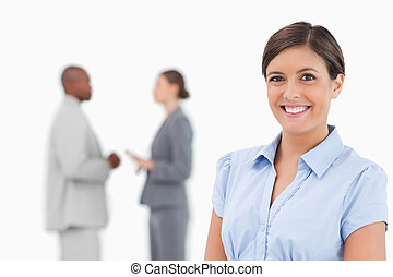 Smiling businesswoman with talking associates behind her
