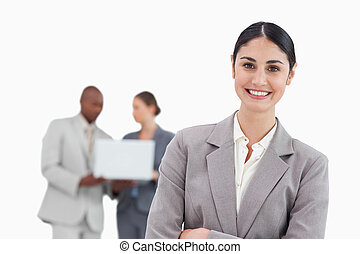 Smiling businesswoman with talking colleagues behind her