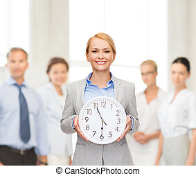 smiling businesswoman with wall clock