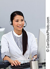 Smiling businesswoman working at a computer
