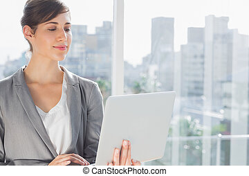 Smiling businesswoman working on laptop