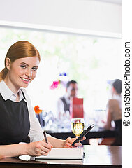Smiling businesswoman writing and holding phone while looking at camera in a restaurant