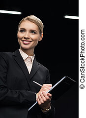 smiling businesswoman writing in notepad isolated on black