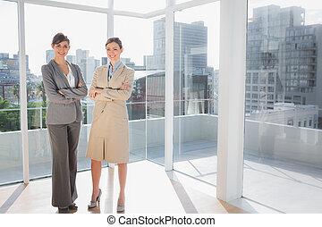 Smiling businesswomen standing in bright office