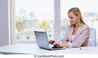 smiling busineswosman with laptop and papers - business,...