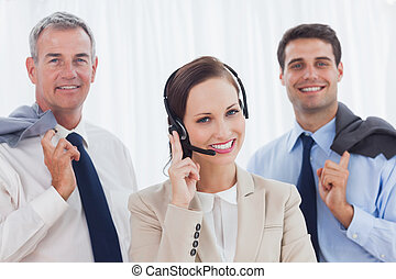 Smiling call center agent posing with her work team in...