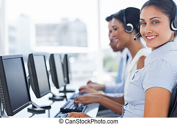 Smiling call center employee looking at camera with...