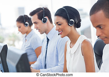 Smiling call center employees sitting in line with their...