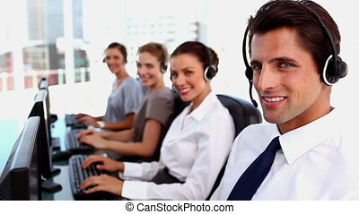 Smiling call centre agent working and looking at the camera
