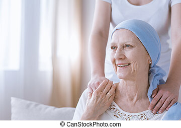 Smiling cancer woman with daughter keeping hands on her arms