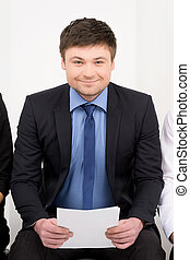 Smiling candidate waiting for interview. Having CV in his hands