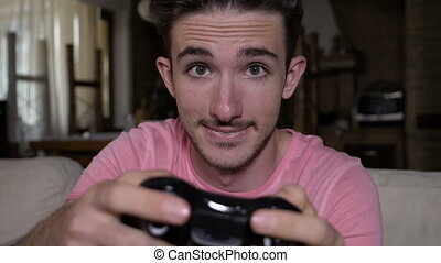 Smiling captivated teenager with game controller having fun...