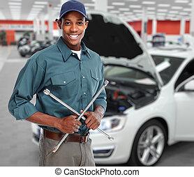 Smiling car mechanic in auto repair service.