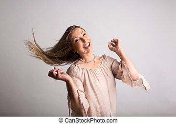 Smiling carefree natural  spirited woman flicking long hair