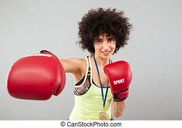 Smiling carefree sports woman boxing at the camera over gray...
