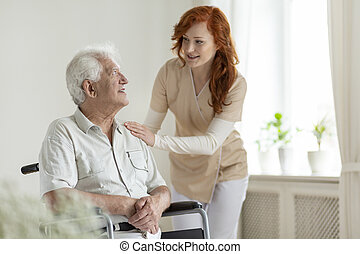 Smiling caregiver helping disabled senior man in the wheelchair