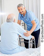 Smiling Caretaker Helping Senior Man With Walking Frame