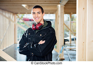Smiling Carpenter Standing Arms Crossed At Site - Portrait...