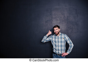 Smiling casual man showing thumb up