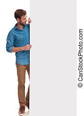 smiling casual man standing behind big blank billboard