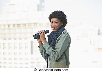 Smiling casual model holding binoculars
