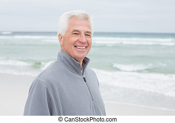 Smiling casual senior man at beach