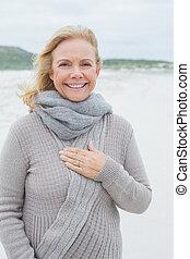 Smiling casual senior woman at beach