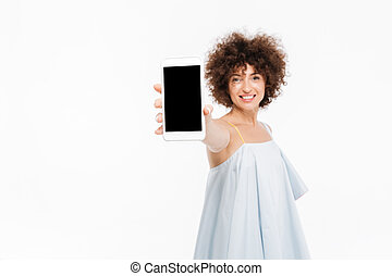 Smiling casual woman showing blank screen mobile phone to camera