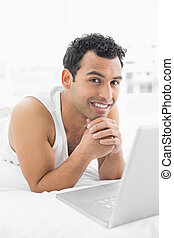 Smiling casual young man using laptop in bed