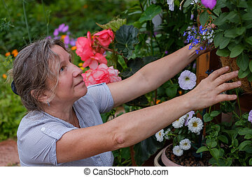 Smiling caucaisan maturehappy woman gardening near the home