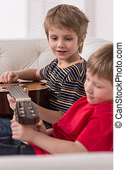 Smiling caucasian boy playing acoustic guitar. boys sitting...