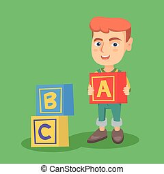 Smiling caucasian boy playing with alphabet cubes.