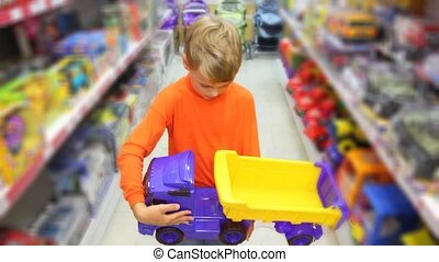 boy with toy auto truck in supermarket