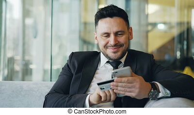 Smiling Caucasian businessman in suit using online banking...