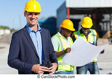 smiling caucasian construction supervisor with binoculars